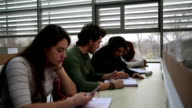 Group of students studying together in the library video