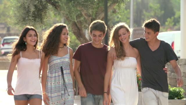 Group Of Teenage Friends Walking Along Street In Slow Motion video