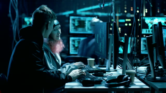 Group of Teenage Hackers Attacking Cyber Security Servers with Virus from Their Underground Hideout. Place Has Dark, Neon Tone, Multiple Displays, Cables Everywhere. video