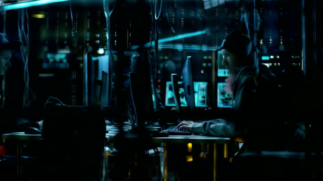 Group of Teenage Hackers Organize Attack on Corporate Data Servers. Their Lair is Dark with Neon Lights and Full of Operating Displays. video