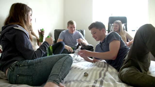Group Of Teenager Drinking Alcohol In Bedroom video