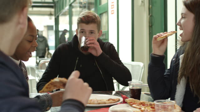 Group Of Teenagers Eating Pizza In Café Shot On R3D video