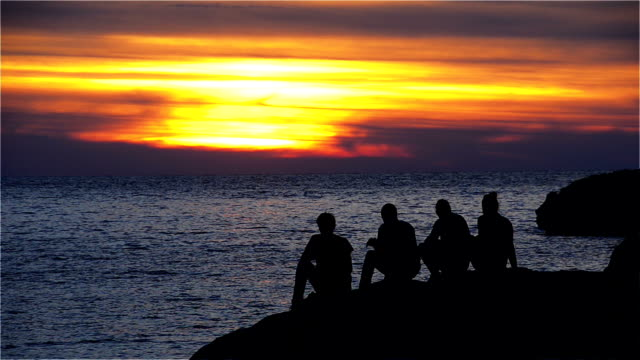 Group of Teenagers Sitting on a Rock and Enjoy the Sunset video