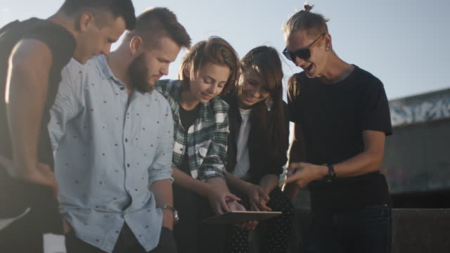 Group of Teenagers Using Tablet Computer for Entertainment Outdoors in Urban Environment video