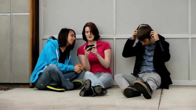 Group of teens outdoors using technology video