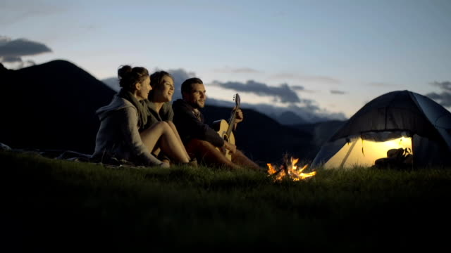 Group of three friends play guitar and sing at camp-fire in nature mountain outdoor camping scene at night - HD video footage video