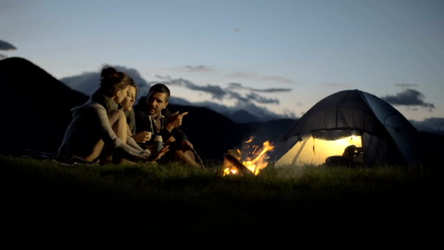 Group of three friends talking, smiling and warming with camp-fire in nature mountain outdoor camping scene at night - HD video footage video