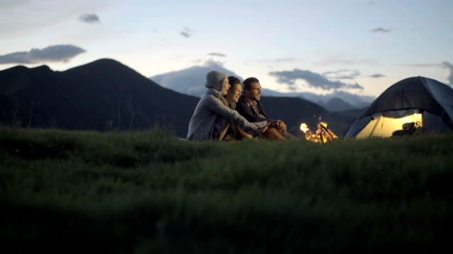 Group of three friends warming with camp-fire in nature mountain outdoor camping scene at night - dolly HD video footage video