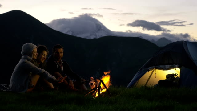 Group of three friends warming with camp-fire in nature mountain outdoor camping scene at night - HD video footage video