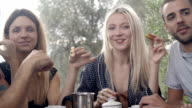 Group of three happy man and women friends smile during italian breakfast in natural rural scenic outdoor during summer sunny day morning in tuscany - slow-motion HD video footage video
