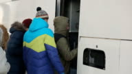 Group of tourists in winter clothes one by one, enter the white bus to go to some city tour video