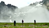 Group of tourists with Hiking backpacks coming in High Snowy Mountains with Clouds in Kavkaz region video
