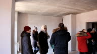 Group of warmly dressed designers and architects in an unfinished room discussing something video