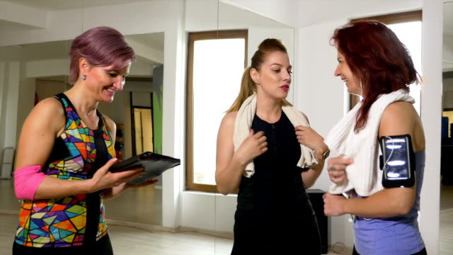 Group of women enjoying conversation about sport activities wearing fitness tracker and smartphone gadgets video