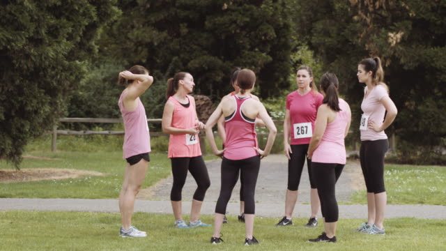 Group of women gathered before a run for breast cancer awareness video