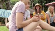 Group of young adults enjoying a fruit dish on the grass video