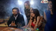 A group of young and beautiful people drinking champagne and playing blackjack video
