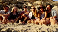 Group of young people at beach with feet in sand video