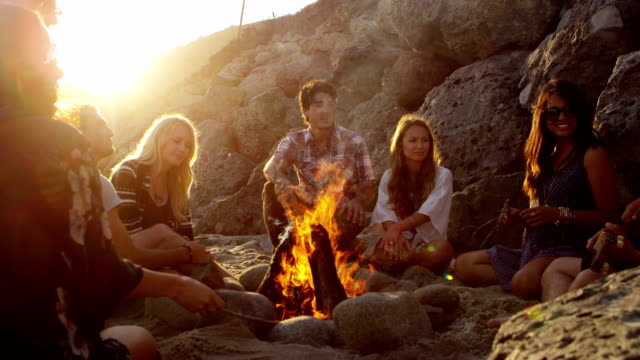 Group of young people hanging out at beach around campfire video