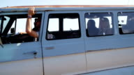Group of young people on road trip driving van video
