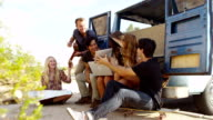 Group of young people on road trip use technology video