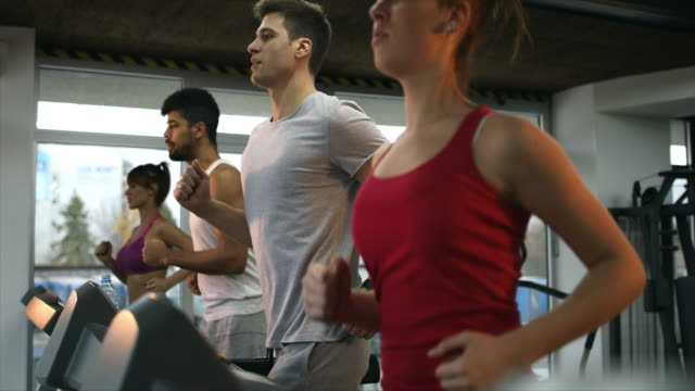 Group of young people running on treadmill in a gym. video