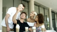 Group of young people sitting in a restaurant and taking a selfies. video
