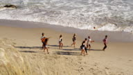 Group of young people walking together along beach video