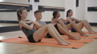A group of young teens doing sit ups in a studio gym video