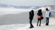 A group of young tourists visit winter lake in mountains and take pictures of landscape video