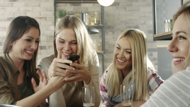 Group of young women looking at phone video