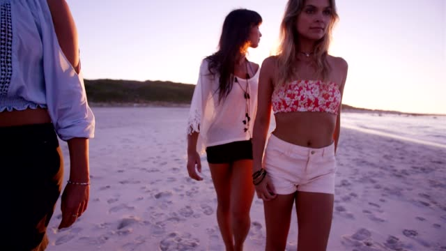 Group of young women walking along the beach video