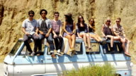 Group portrait of young people sitting together on van video