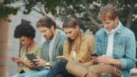 Group sitting on bench with their mobile devices video