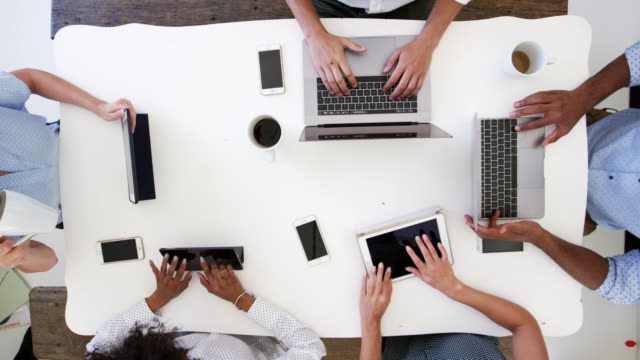 Group work on computers with phones, overhead shot, slo mo video