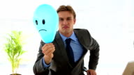 Grumpy businessman holding sad face balloon video