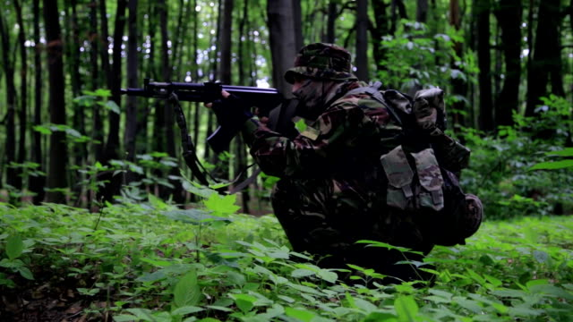 Guerilla partisan warrior aiming in forest ambush carrying his gun video