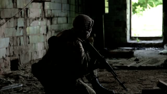 Guerilla partisan warrior operation in urban environment. Soldier aiming an enemy with his gun video