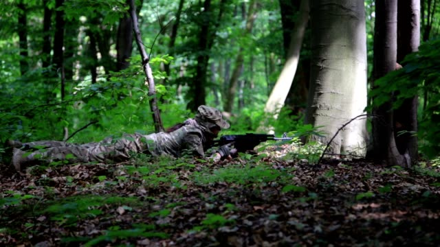 Guerilla partisan warrior sniper aiming in forest ambush carrying his gun video
