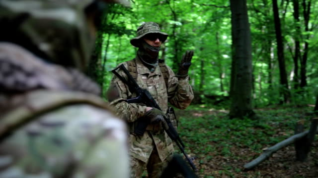 Guerilla warriors squad commander instructing his fighters in the forest bushes video