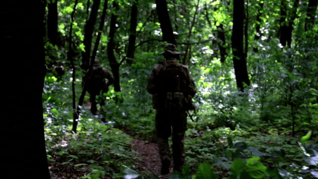 Guerilla warriors squad running in one formation carrying their guns in the forest bushes video