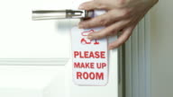 Guest hanging make up room sign on the door of hotel room video