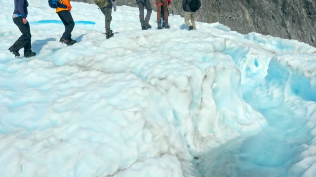 Guide to break the glaciers, Walking through glacier tunnel with guide using ice pick. Fox Glacier, New Zealand video