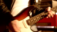 Guitarist. Close-up on a male hand playing hard on a electric guitar. Blurry amplifier & speaker box in background. video