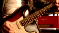 Guitarist. Close-up on a male hand starting playing electric guitar. Blurry amplifier & speaker box in background. video