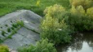 Gull flies over a prairie waterway over dam in slowmotion video