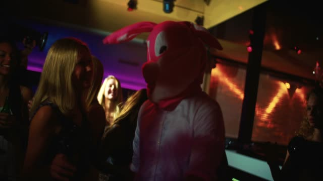 Guy as bunny at party club next young woman dancing video