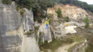 AERIAL: Guy highlining with backup over abyss, trying to balance and falling video