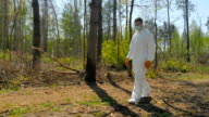 A guy in a special suit removes trash in forest video