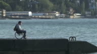Guy In Wheelchair Throws Stones In Water video